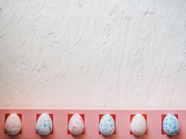 Oeufs en mousse blanche sur fond bleu. mise à plat, vue de dessus. concept de pâques