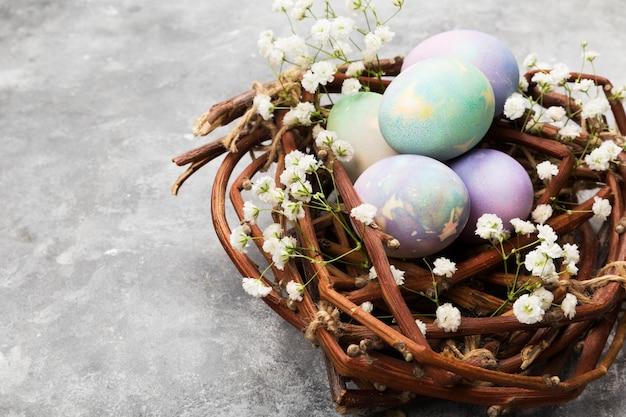 Oeufs multicolores pour pâques dans un nid avec des fleurs sur fond gris. copiez l'espace. contexte alimentaire