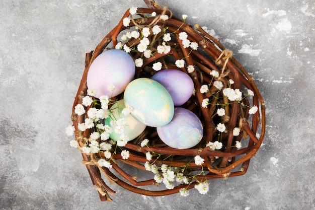 Oeufs multicolores pour pâques dans un nid avec des fleurs sur fond gris. vue de dessus. contexte alimentaire