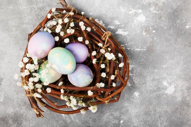 Oeufs multicolores pour pâques dans un nid avec des fleurs sur fond gris. vue de dessus, espace copie. contexte alimentaire