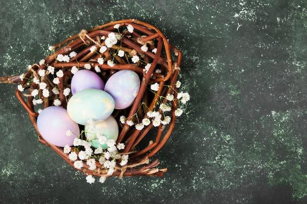 Oeufs multicolores pour pâques dans un nid avec des fleurs sur fond vert. vue de dessus, espace copie. contexte alimentaire