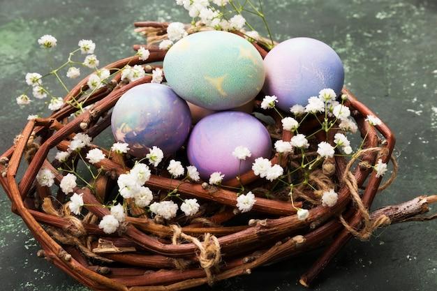 Oeufs multicolores pour pâques dans un nid avec des fleurs sur fond vert