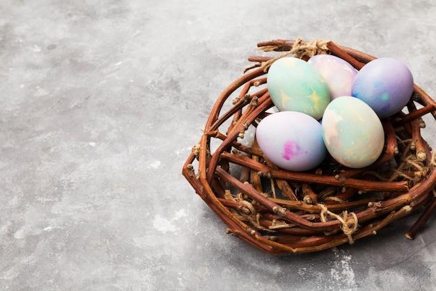 Oeufs multicolores pour pâques en nid sur fond gris. copiez l'espace. contexte alimentaire