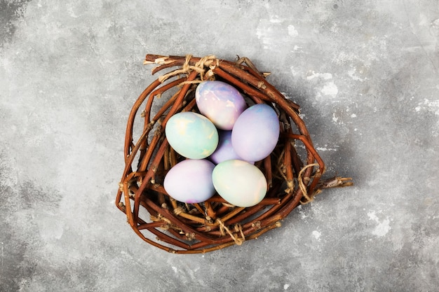 Oeufs multicolores pour pâques en nid sur fond gris. vue de dessus. contexte alimentaire