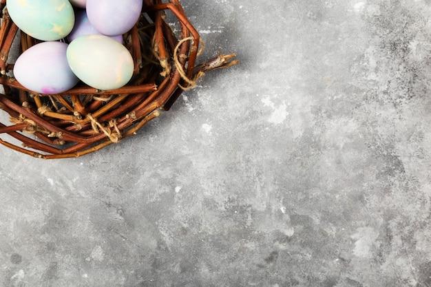 Oeufs multicolores pour pâques en nid sur fond gris. vue de dessus, espace copie. contexte alimentaire