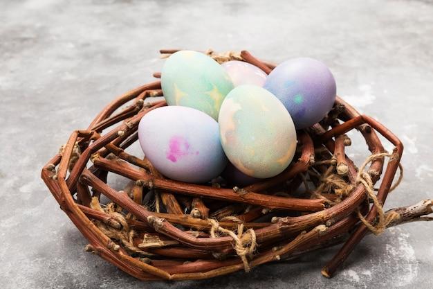 Oeufs multicolores pour pâques en nid sur fond gris