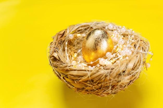 Oeufs d'or dans le nid sur fond jaune, joyeuses pâques