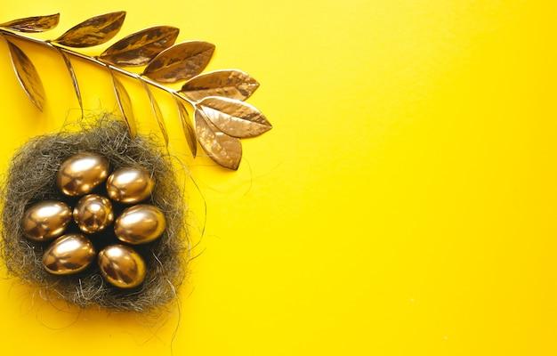 Les œufs d'or dans un panier avec nid de paille sur un tableau jaune