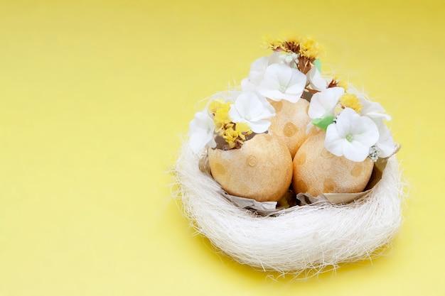 Oeufs d'or avec des fleurs dans un nid sur une surface jaune