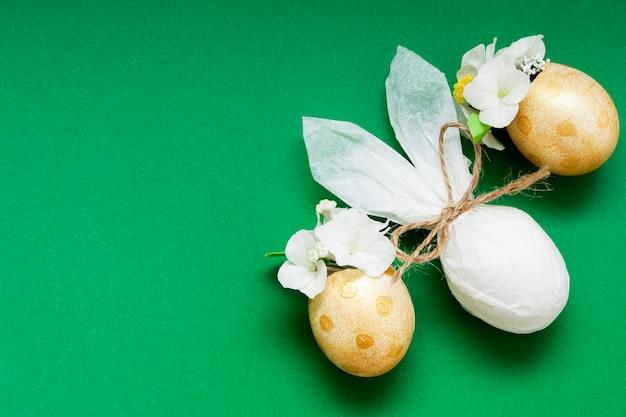 Oeufs d'or avec fleurs et lapin abstrait sur une surface verte