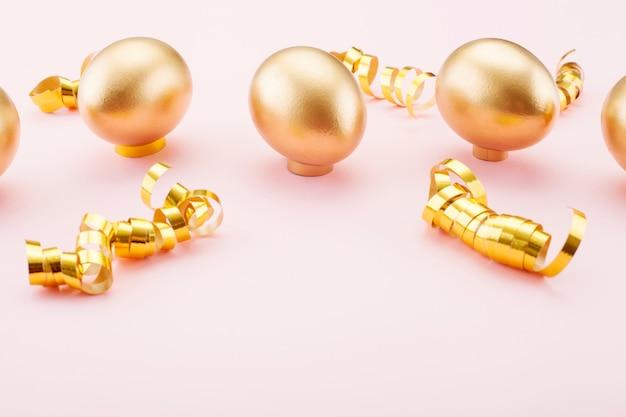 Oeufs d'or sur fond rose, ornés de rubans dorés. le concept de pâque et le symbole des vacances.