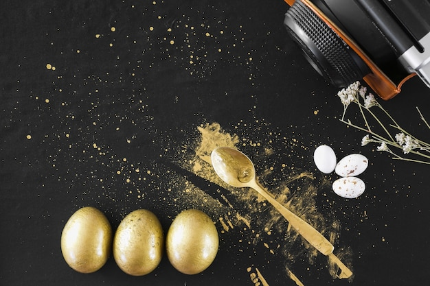 Oeufs d'or près de cuillère et caméra