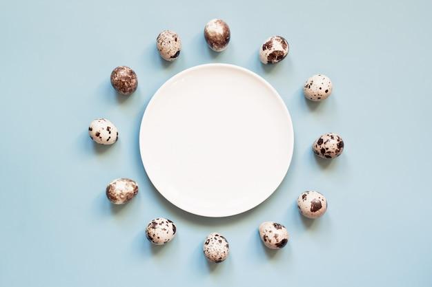 Oeufs de pâques et assiette blanche sur bleu pastel