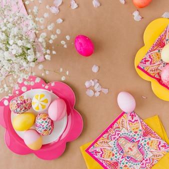 Oeufs de pâques sur des assiettes près des serviettes et des fleurs