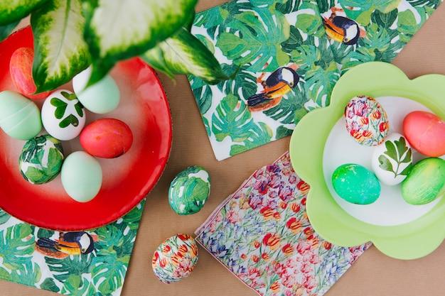 Oeufs de pâques sur des assiettes près de serviettes avec des peintures tropicales