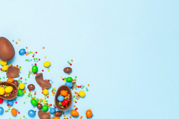 Oeufs de pâques au chocolat cassés et entiers, bonbons multicolores sur fond bleu. concept de célébrer pâques, décorations de pâques, recherche de bonbons pour le lapin de pâques. mise à plat, vue de dessus. copiez l'espace.