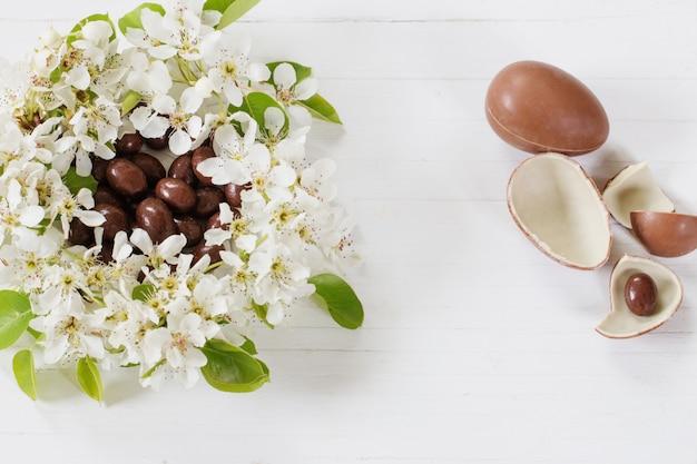 Oeufs de pâques au chocolat avec des fleurs de printemps sur fond de bois