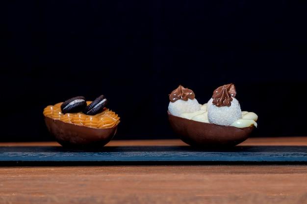 Oeufs de pâques au chocolat sur pierre noire avec fond en bois