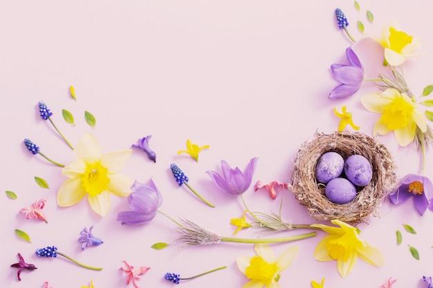 Oeufs de pâques au nid avec des fleurs de printemps