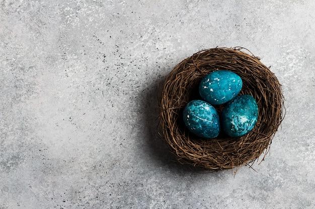 Oeufs de pâques au nid peints à la main en bleu