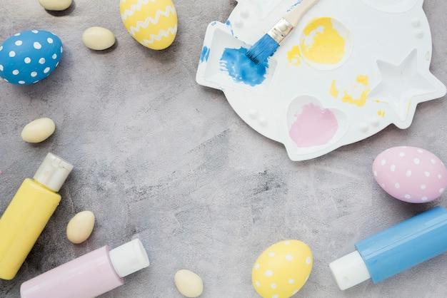 Oeufs de pâques avec des bâtons de colle et de la palette de peinture sur la table