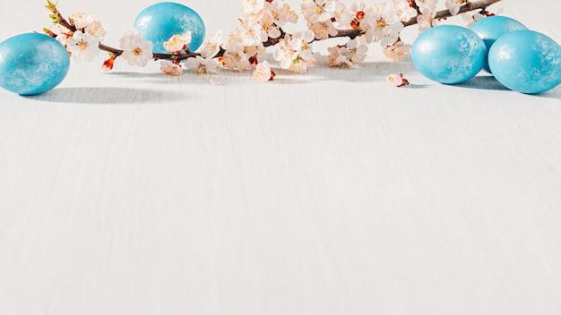 Oeufs de pâques bleu avec branche d'abricot en fleurs