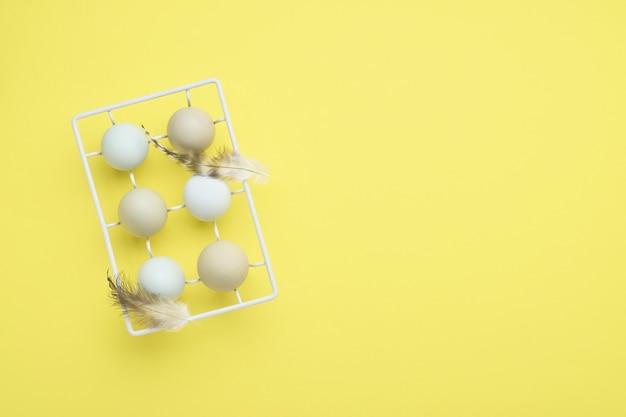 Oeufs de pâques bleu clair dans un support en métal vintage blanc avec des plumes jaunes sur la table. vue de dessus