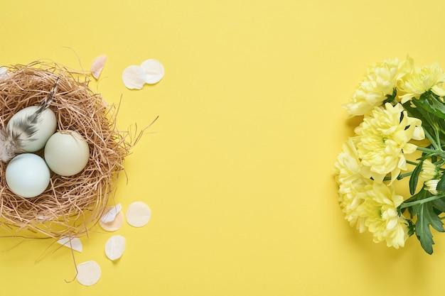 Oeufs de pâques bleu clair dans un support en métal vintage blanc avec plumes, ruban, fleurs de chrysanthèmes jaunes et papier vierge pour texte sur fond jaune. maquette.