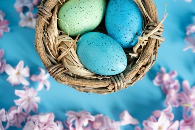 Oeufs de pâques bleus dans un nid de fleurs printanières. vue de dessus avec espace copie.