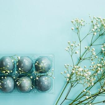 Oeufs de pâques bleus délicats parmi les fleurs de gypsophila sur fond bleu.