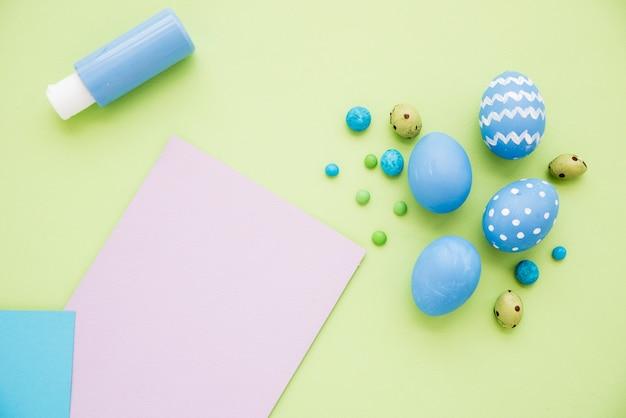 Oeufs de pâques bleus avec une feuille de papier sur la table