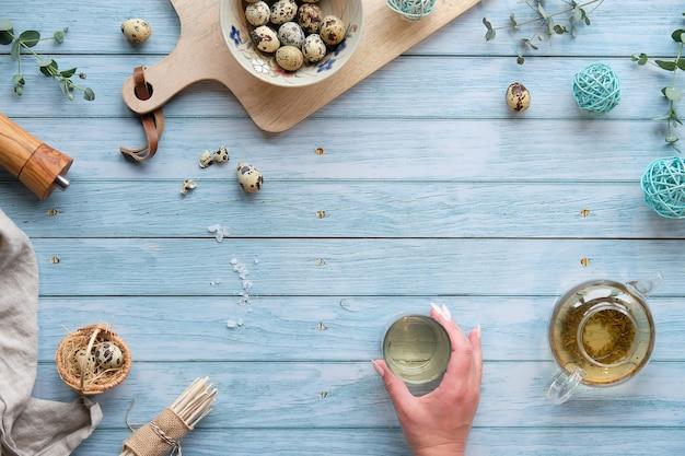 Oeufs de pâques de caille et décorations printanières naturelles, brindilles et eucalyptus. main avec verre