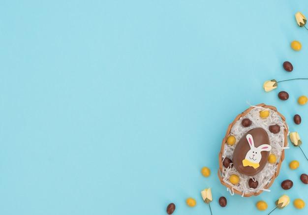 Oeufs de pâques en chocolat brun et jaune de couleur dans le panier d'oeufs avec du papier blanc et des fleurs de printemps sur bleu