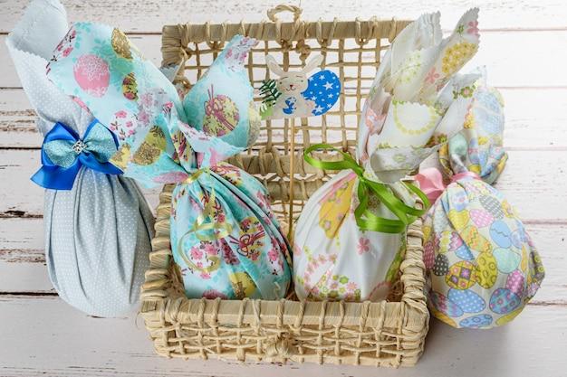 Œufs de pâques en chocolat emballés avec des tissus colorés et des nœuds en ruban. sur un panier de paille de maïs.