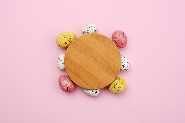 Oeufs de pâques colorés, autour de support en bois sur fond rose