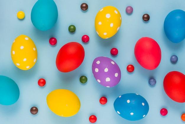 Oeufs de pâques colorés avec des bonbons sur la table bleue