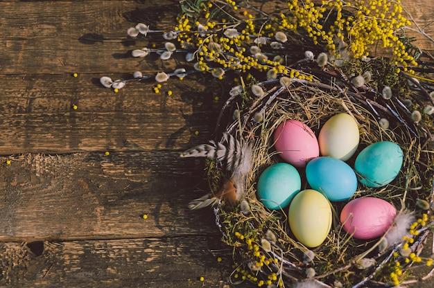 Oeufs de pâques colorés dans un beau nid. dans le contexte d'une vieille planche de bois.
