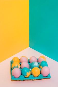 Oeufs de pâques colorés dans un grand rack sur une table lumineuse