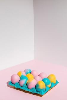 Oeufs de pâques colorés dans un grand rack sur la table rose