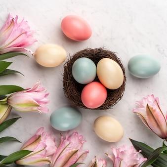 Oeufs de pâques colorés dans le nid avec fleur de lys rose sur une surface de table en marbre blanc brillant.