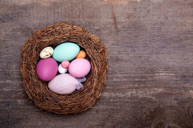 Oeufs de pâques colorés dans le nid sur fond de bois rustique avec espace de copie pour le texte. concept minimal de pâques avec surface.