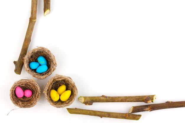 Oeufs de pâques colorés dans des nids isolés sur blanc