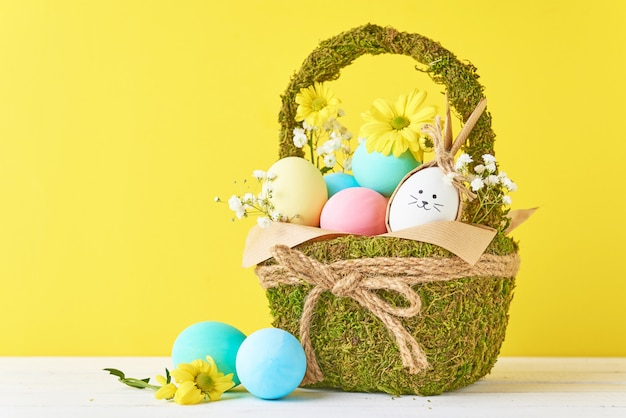 Oeufs de pâques colorés dans le panier avec des décorations de fleurs sur fond jaune