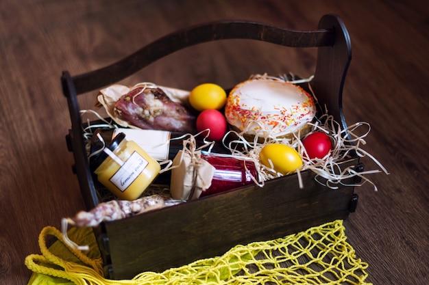 Oeufs de pâques colorés dans un panier avec gâteau, vin rouge, hamon ou saucisse fumée et séchée