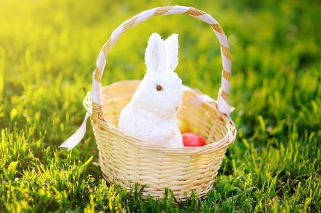 Oeufs de pâques colorés dans un panier avec lapin mignon jouet blanc