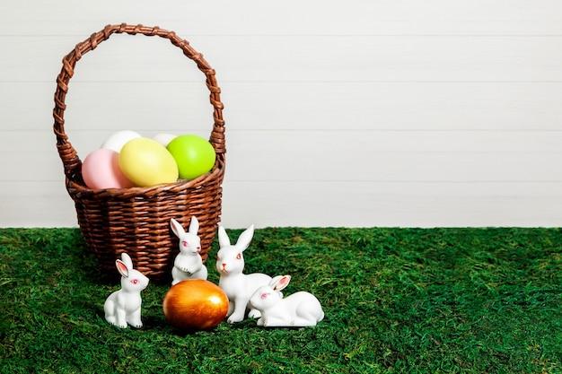 Oeufs de pâques colorés dans un panier avec de petits lapins blancs autour de l'oeuf d'or