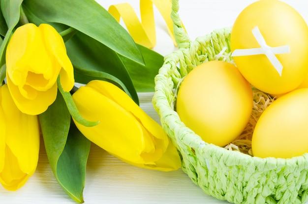Oeufs de pâques colorés dans le panier vert et bouquet de tulipes sur un fond en bois blanc. concept de vacances de pâques.