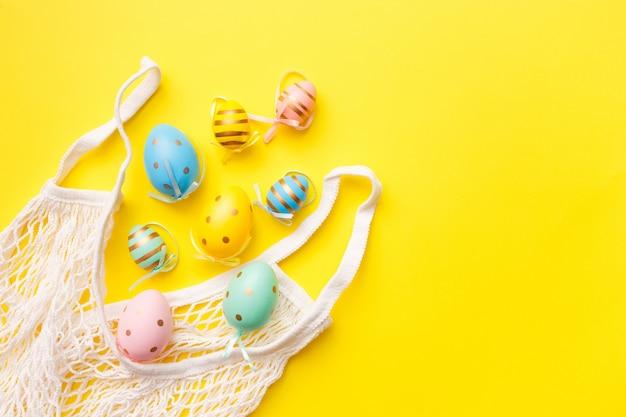 Oeufs de pâques colorés dans un sac sur fond jaune. concept de carte de voeux de joyeuses pâques. vue de dessus, pose à plat