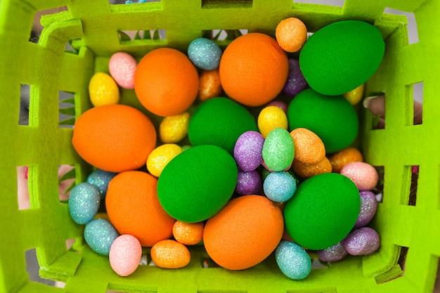 Oeufs de pâques colorés de différentes tailles dans un panier