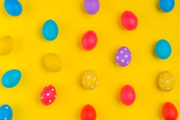 Oeufs de pâques colorés dispersés sur une table jaune